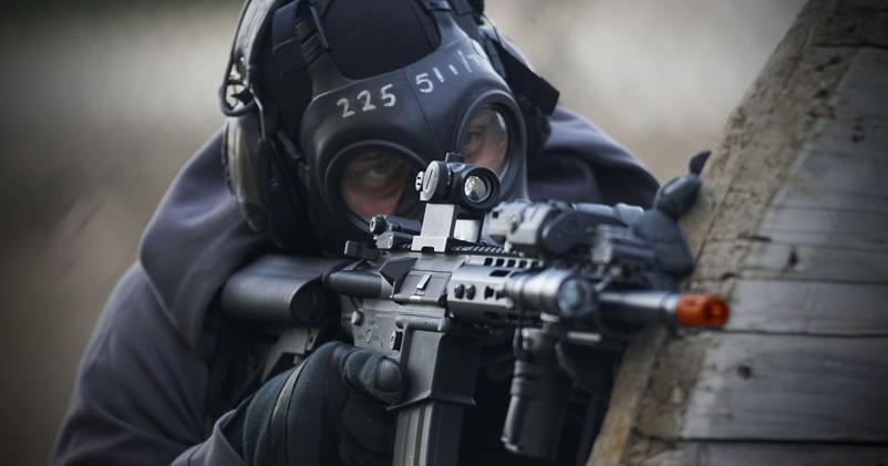 Pessoa com arma airsoft na mão, se escondendo de inimigo